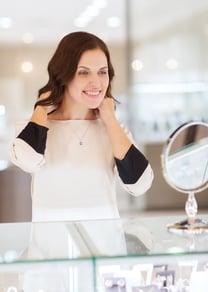 happy-woman-choosing-pendant-at-jewelry-store-487418836_2925x4107